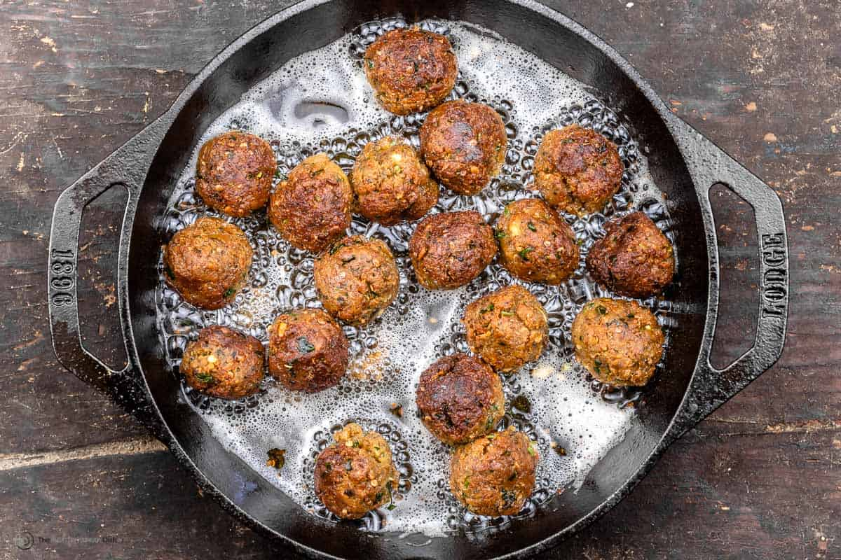 Eggplant meatballs being cooked in a skillet of sizzling oil
