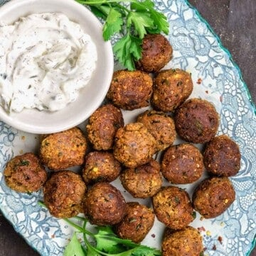 Vegan meatballs with eggplant on a blue plate, next to a dish of tzatziki