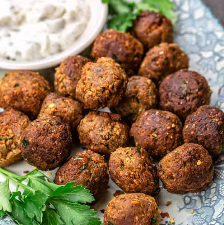 Eggplant meatballs on a blue plate, with a dish of tzatziki and garnished with parsley