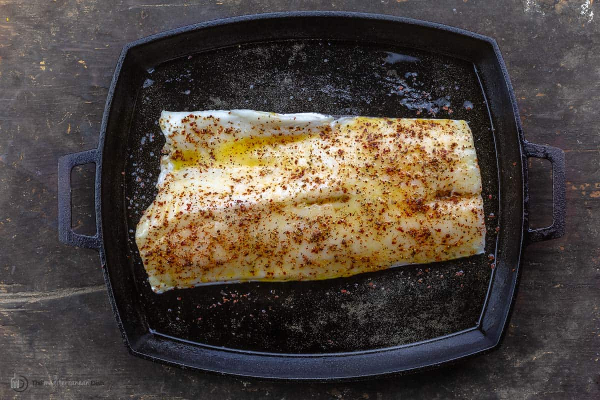 A sea bass fillet in a black pan