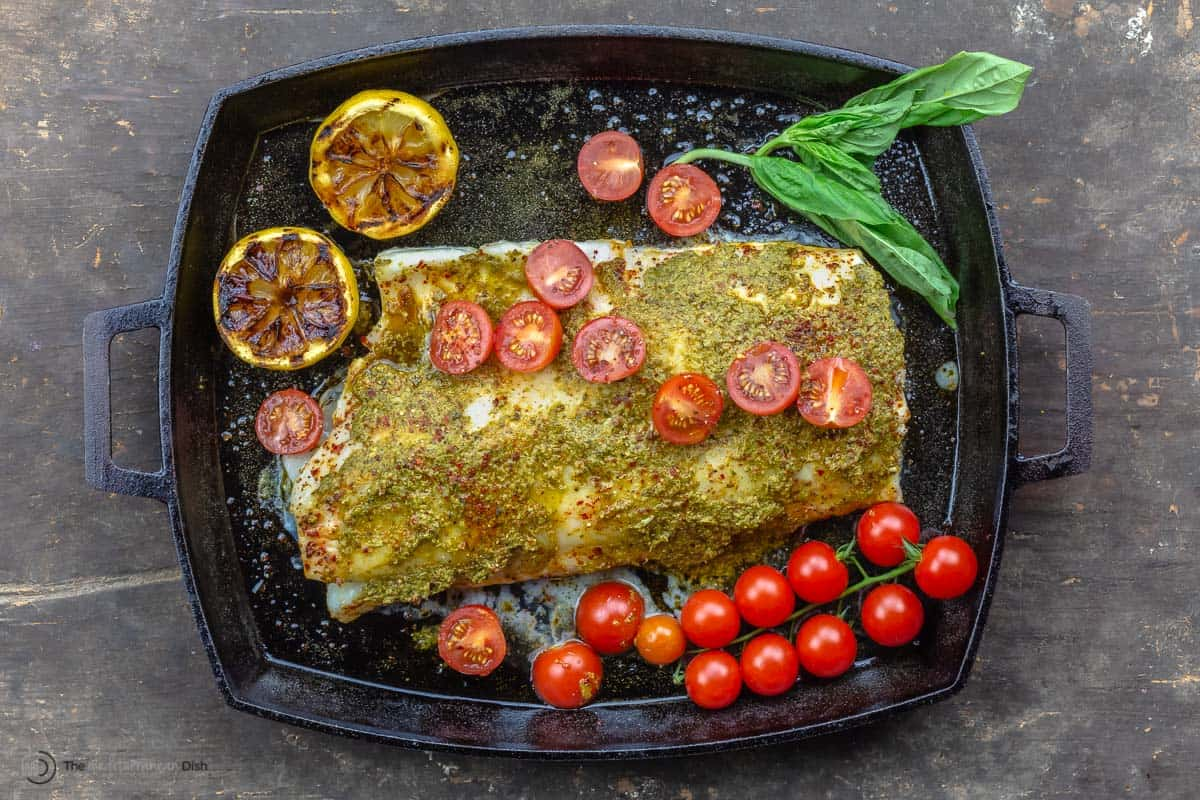A baked sea bass fillet topped with pesto and grape tomatoes