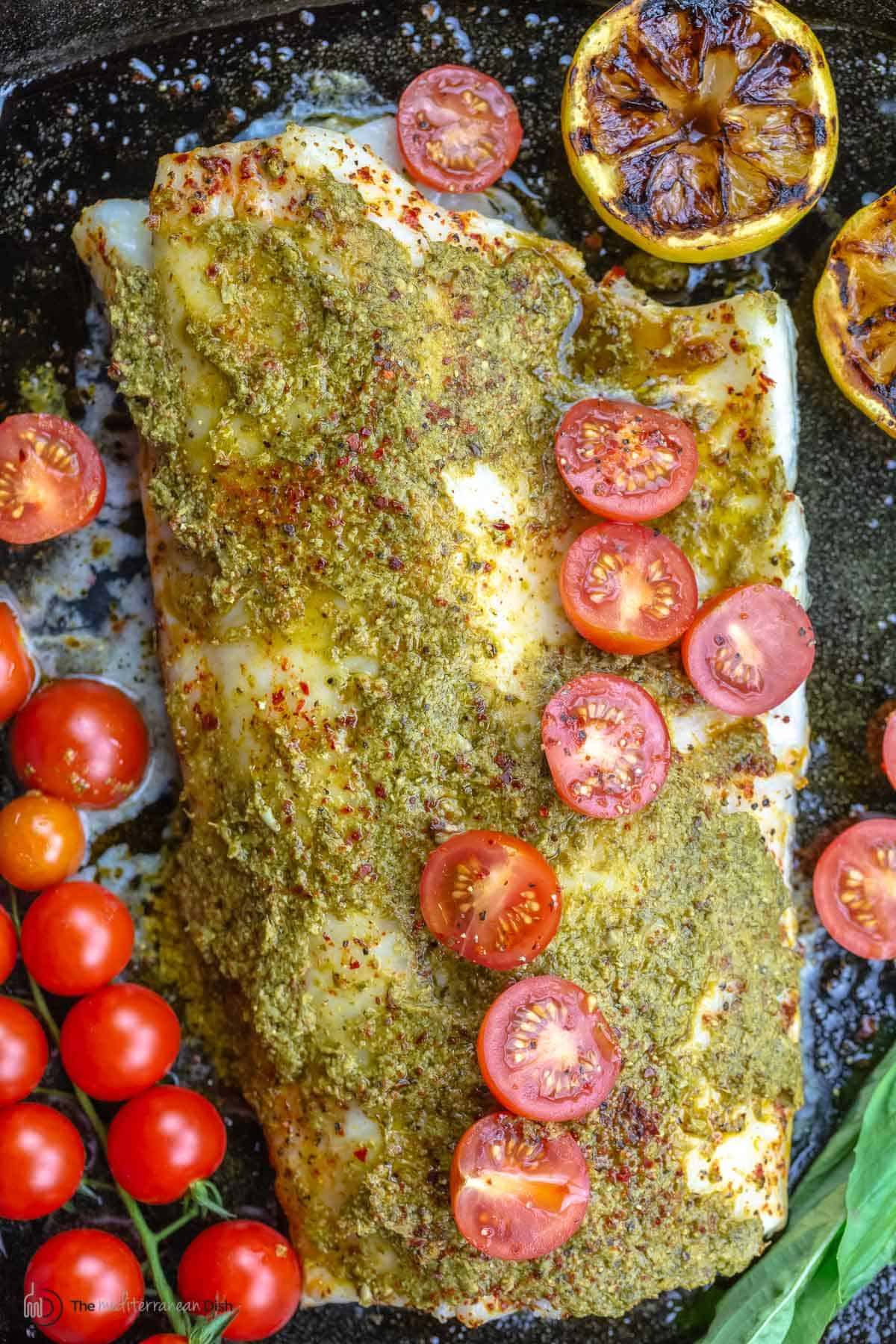 Baked sea bass topped with pesto and grape tomato halves