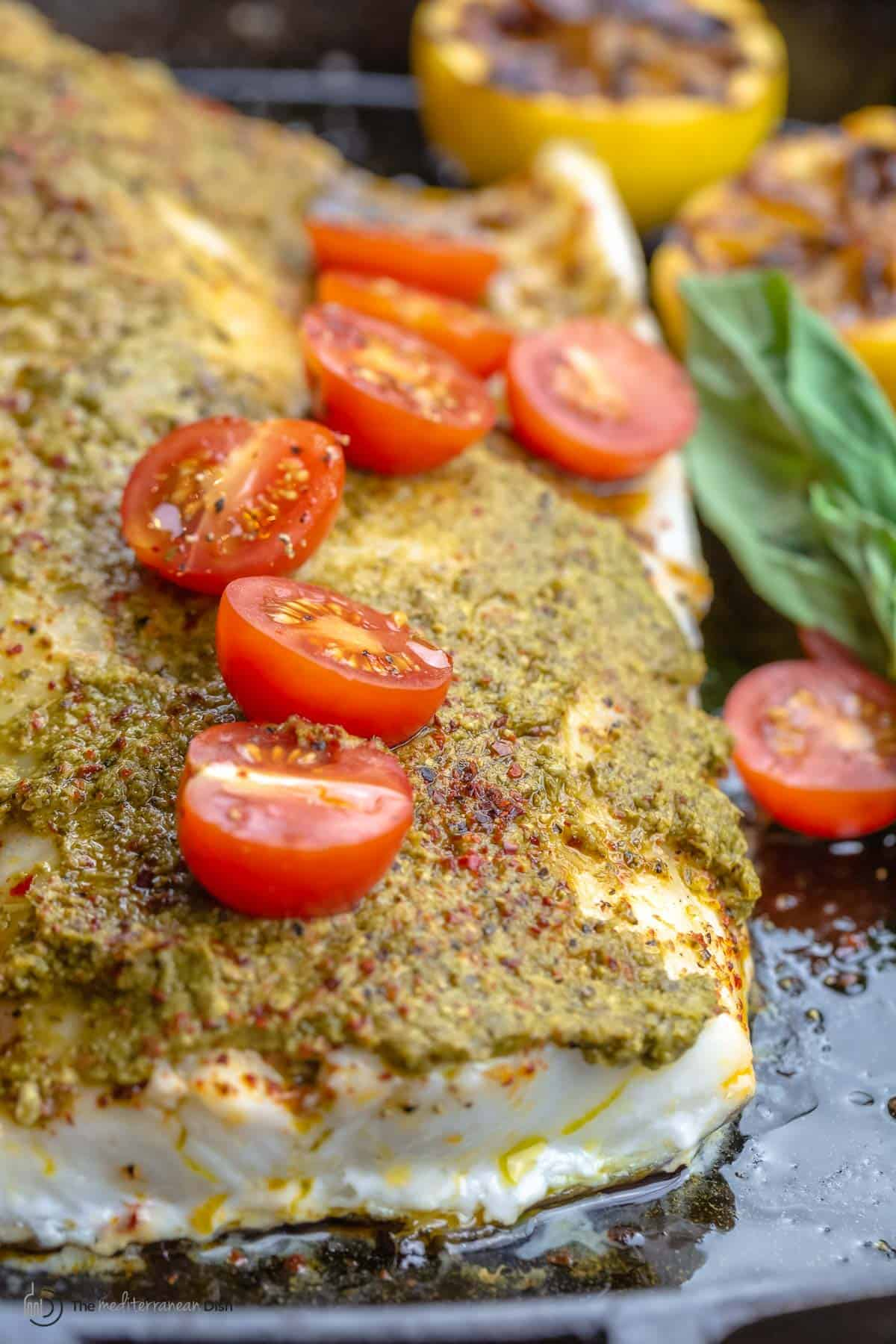 Close-up of a baked sea bass fillet with basil pesto and grape tomato halves