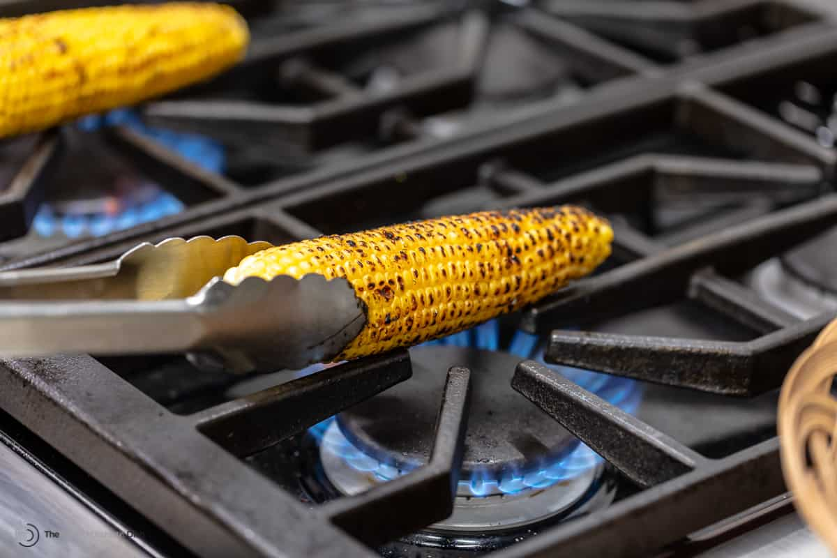 An ear of corn being turned over the flame of a gas burner