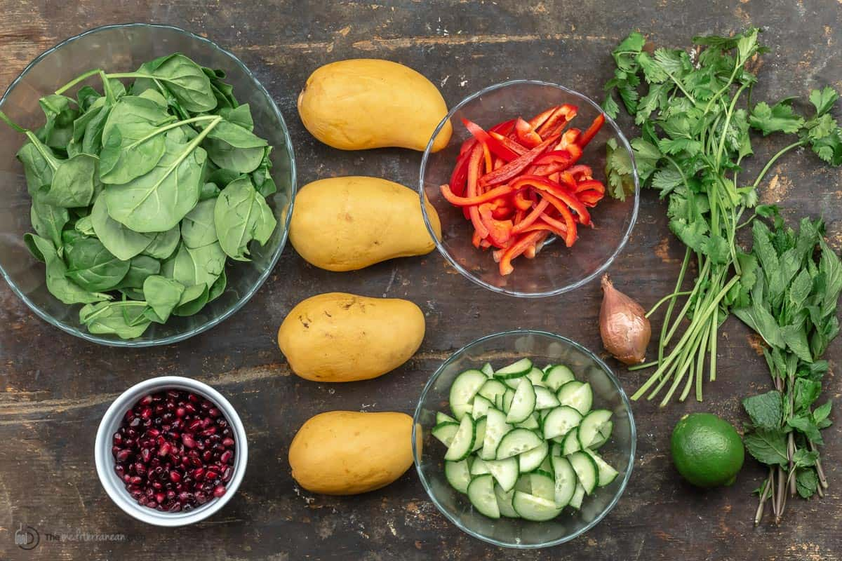 Overhead view of mango salad ingredients - spinach, pomegranate seeds, mangos, cucumbers, peppers, shallots, lime