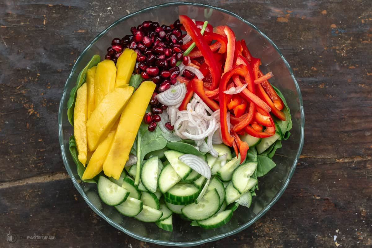 All of the ingredients to make mango spinach salad in a glass bowl