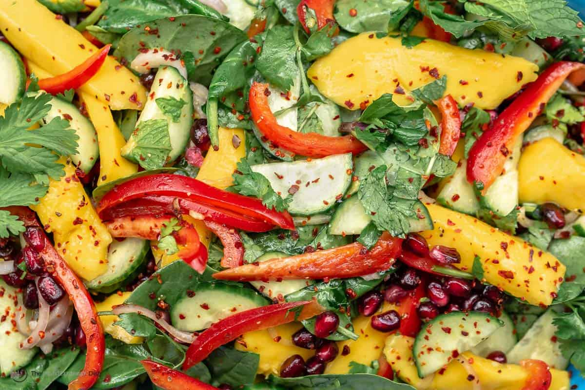 A close-up of healthy mango salad with spinach