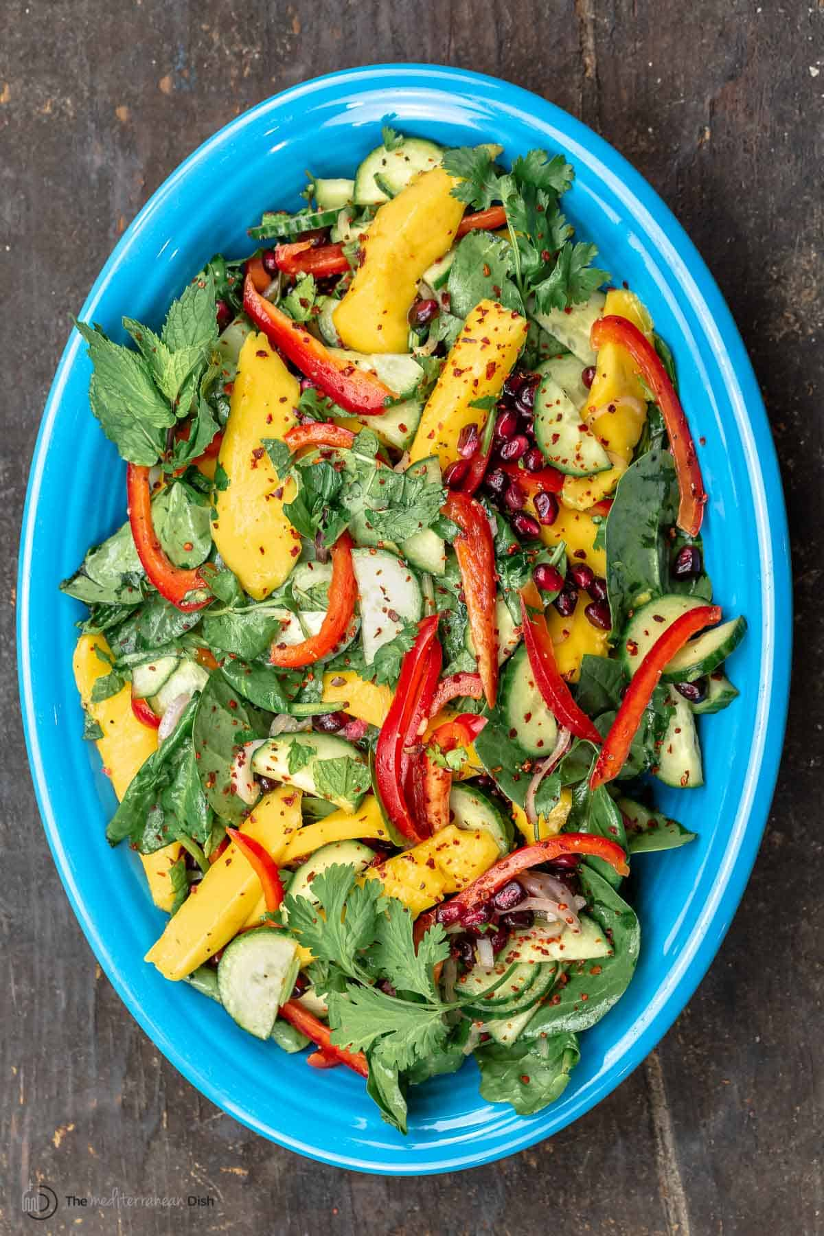Healthy mango salad on a blue serving plate