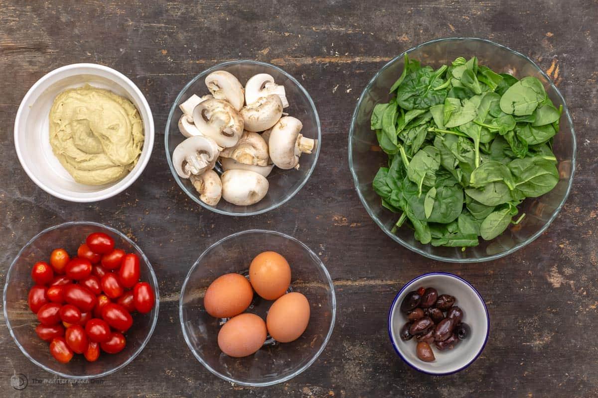 Hummus, mushrooms, spinach, tomatoes, eggs and seasonings all in individual bowls