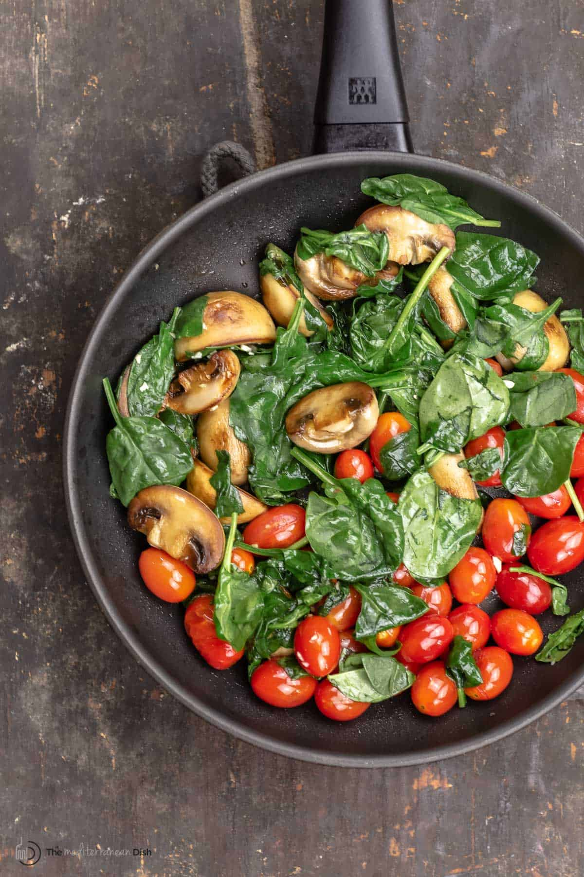 Mushrooms, spinach and cherry tomatoes in a skillet