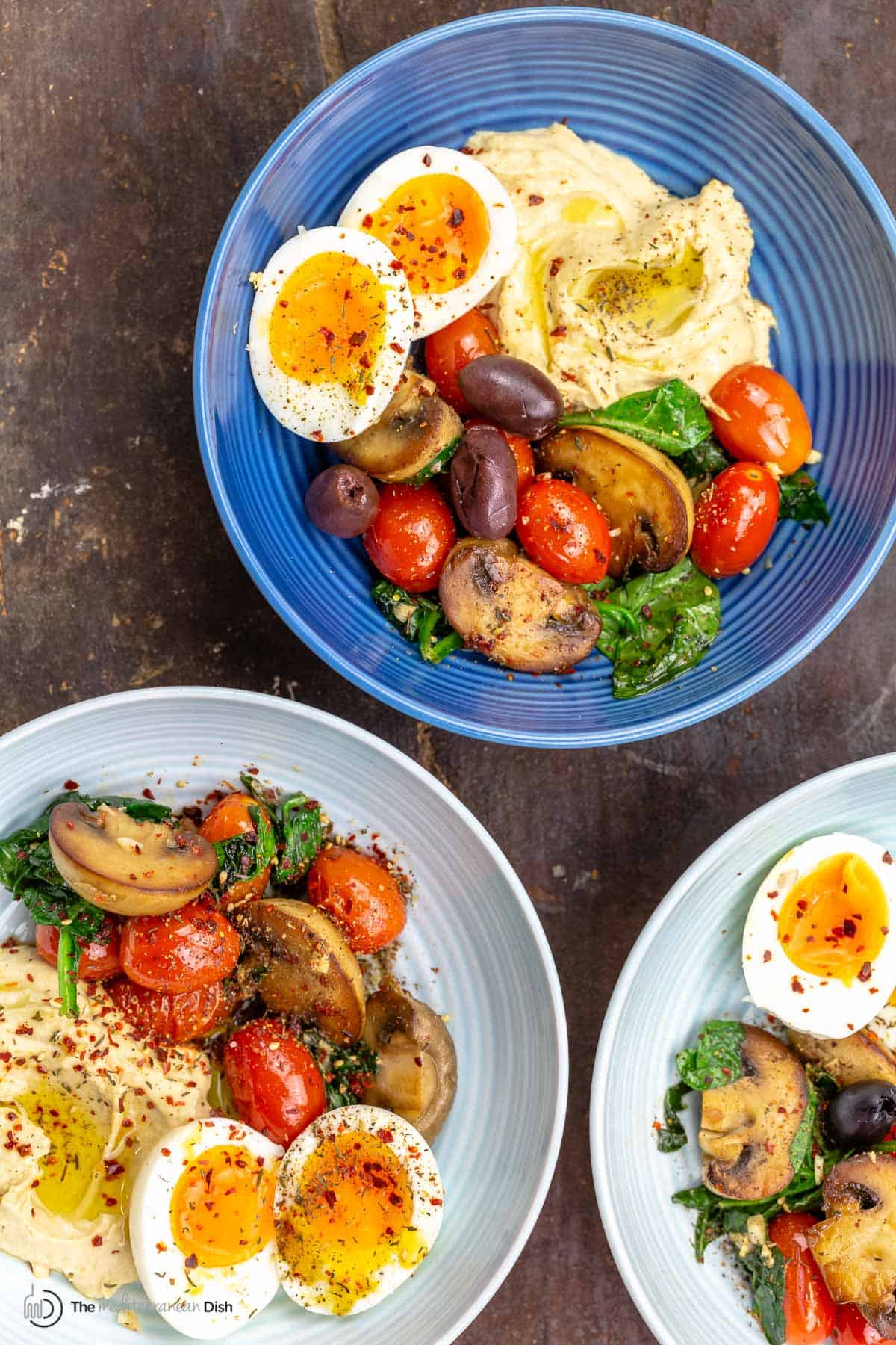 Two savory breakfast bowls with eggs, vegetables and hummus