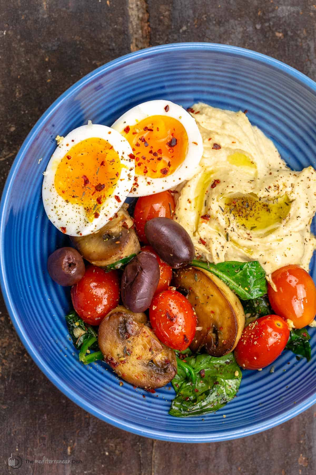 A Mediterranean breakfast bowl with a soft-boiled egg, hummus and sauteed vegetables on a blue plate.
