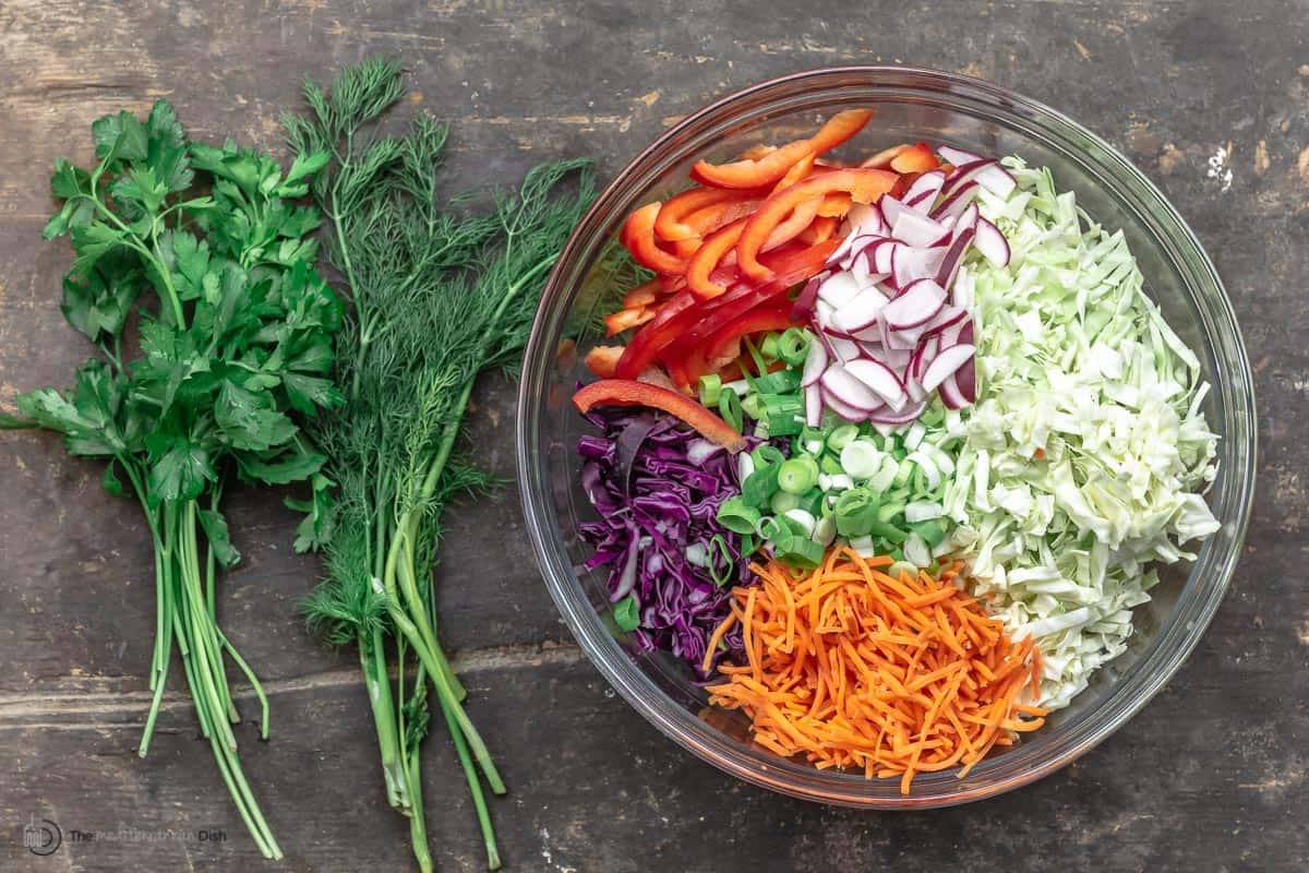A bowl of chopped veggies - red peppers, cabbage, carrots, radishes - next to two bunches of fresh herbs