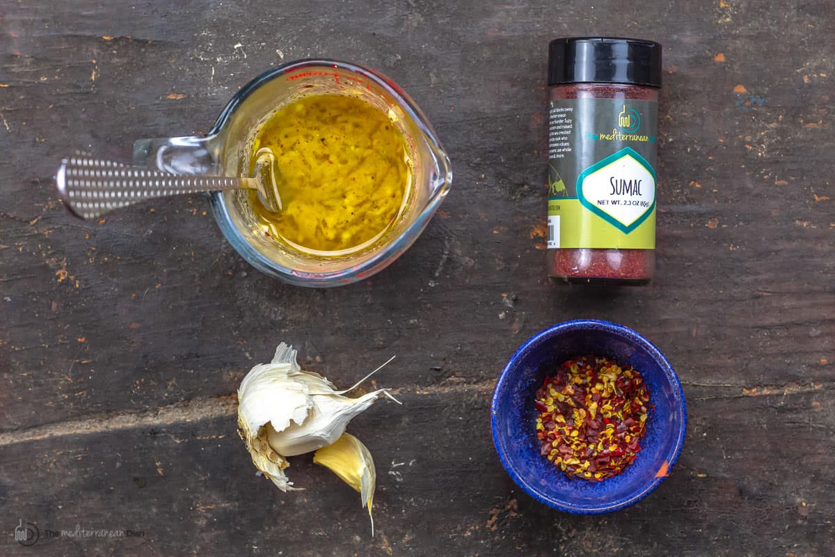 A measuring cup with dijon mustard and lemon juice, a shaker of Sumac, garlic and a dish of spices