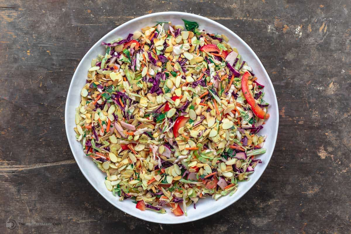 A large bowl of Mediterranean Cabbage Salad with Mustard Vinaigrette