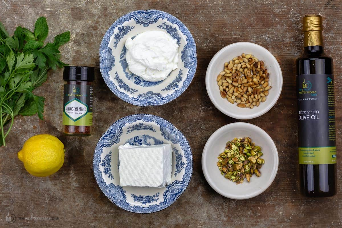Greek yogurt, feta cheese, pine nuts and crushed pistachios measured into bowls with a lemon, aleppo pepper and olive oil on the sides