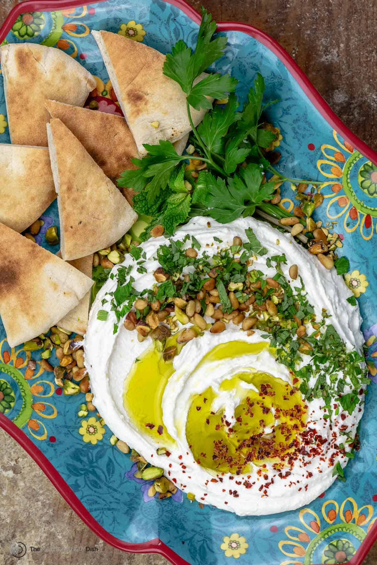Whipped feta cheese topped with olive oil and fresh herbs on a tray with pita chips