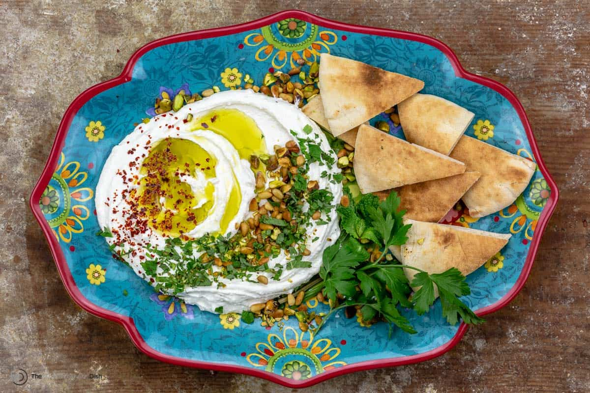Whipped feta dip topped with olive oil and herbs, served with pita chips, on a blue plate