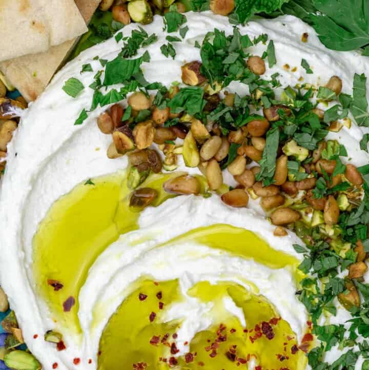 A close-up of whipped feta with olive oil, pine nuts, pistachios and herbs