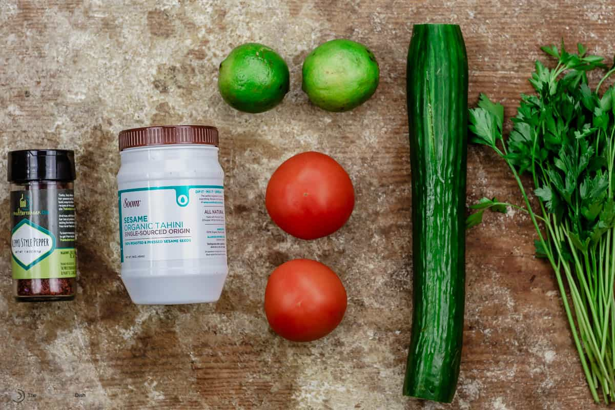A jar of Aleppo pepper, tahini, two limes, two tomatoes, a cucumber and fresh parsley