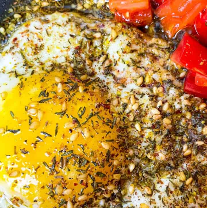 fried eggs with olive oil and za'atar and a side of chopped cherry tomatoes