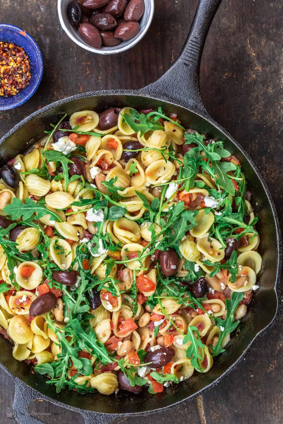 Orecchiette pasta in a skillet, topped with arugula. smaller bowls of red pepper flakes and olives to the side