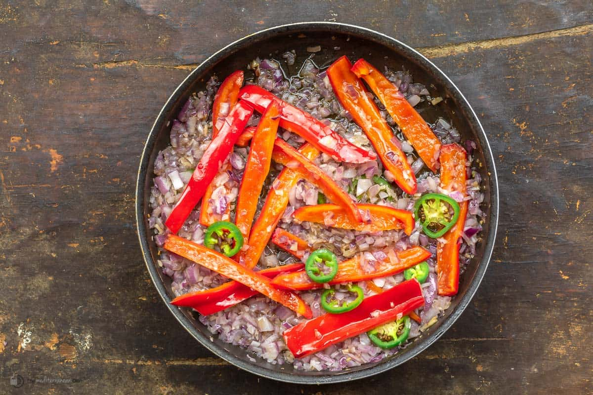 A large skillet with chopped onions, red peppers, jalapenos and garlic