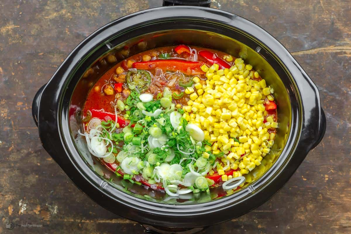 Scallions and corn being added to slow cooker chili