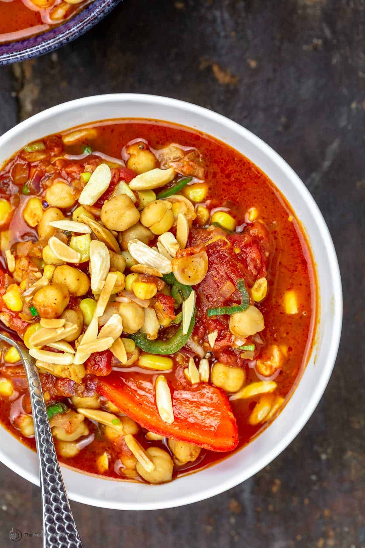 A big bowl of chickpea chili topped with toasted almonds