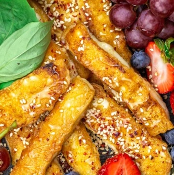Fried halloumi on a plate with fruit and honey