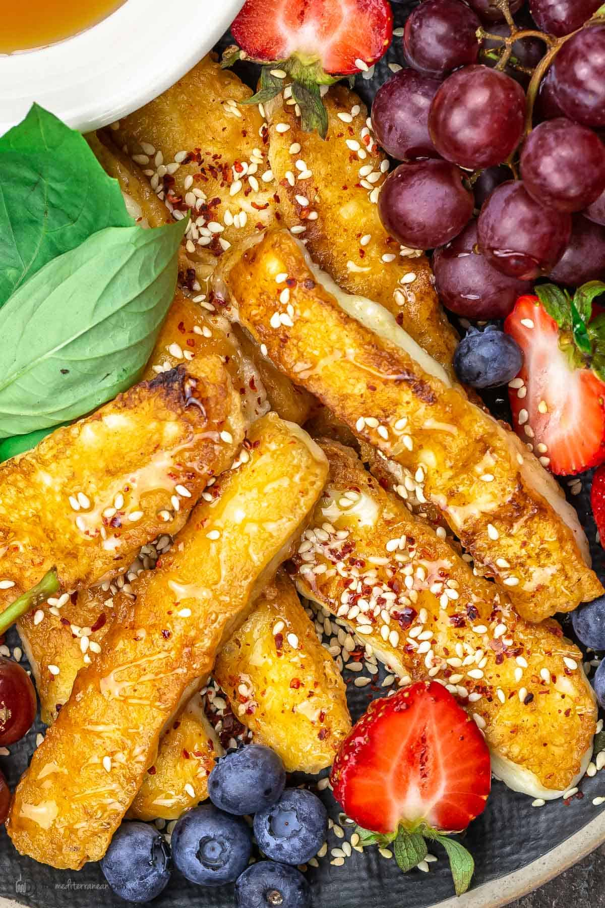 fried halloumi on a platter with fruit and honey