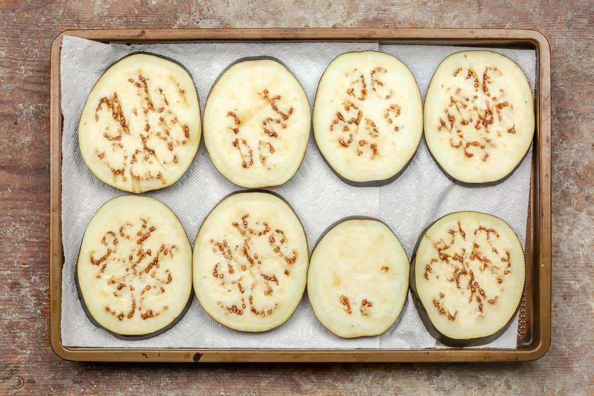Salt eggplant slices on a baking tray