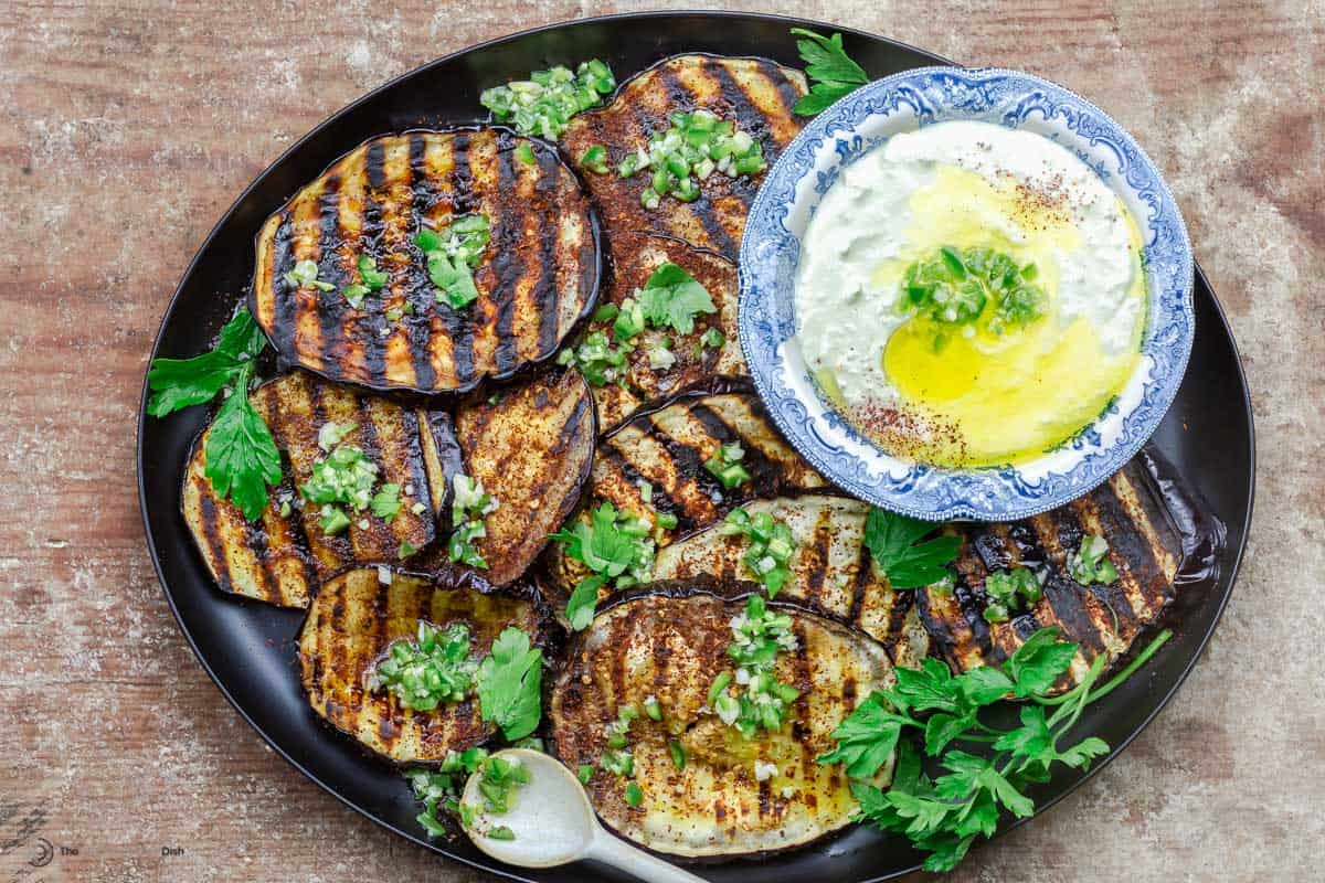 Mediterranean grilled eggplant slices on a plate with whipped feta dip