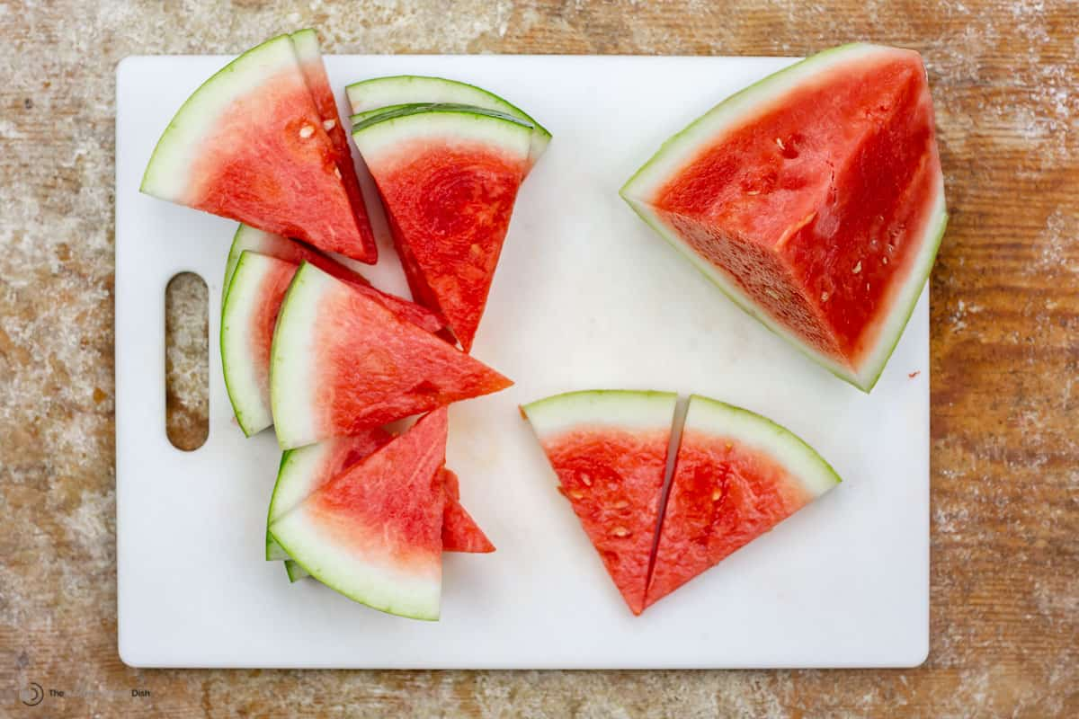 Watermelon slices into triangles on a cutting board