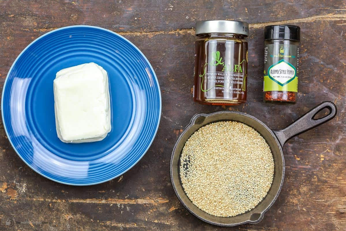 A brick of halloumi on a plate, honey, Aleppo pepper and sesame seeds.