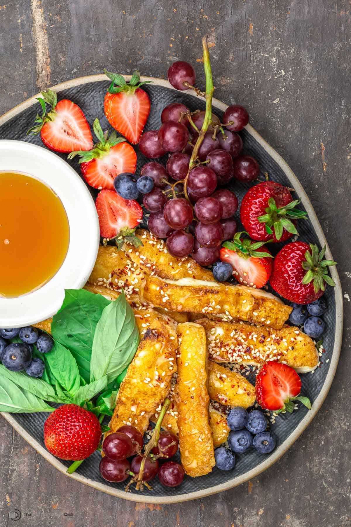 Halloumi fries on a serving plate with fruit and honey