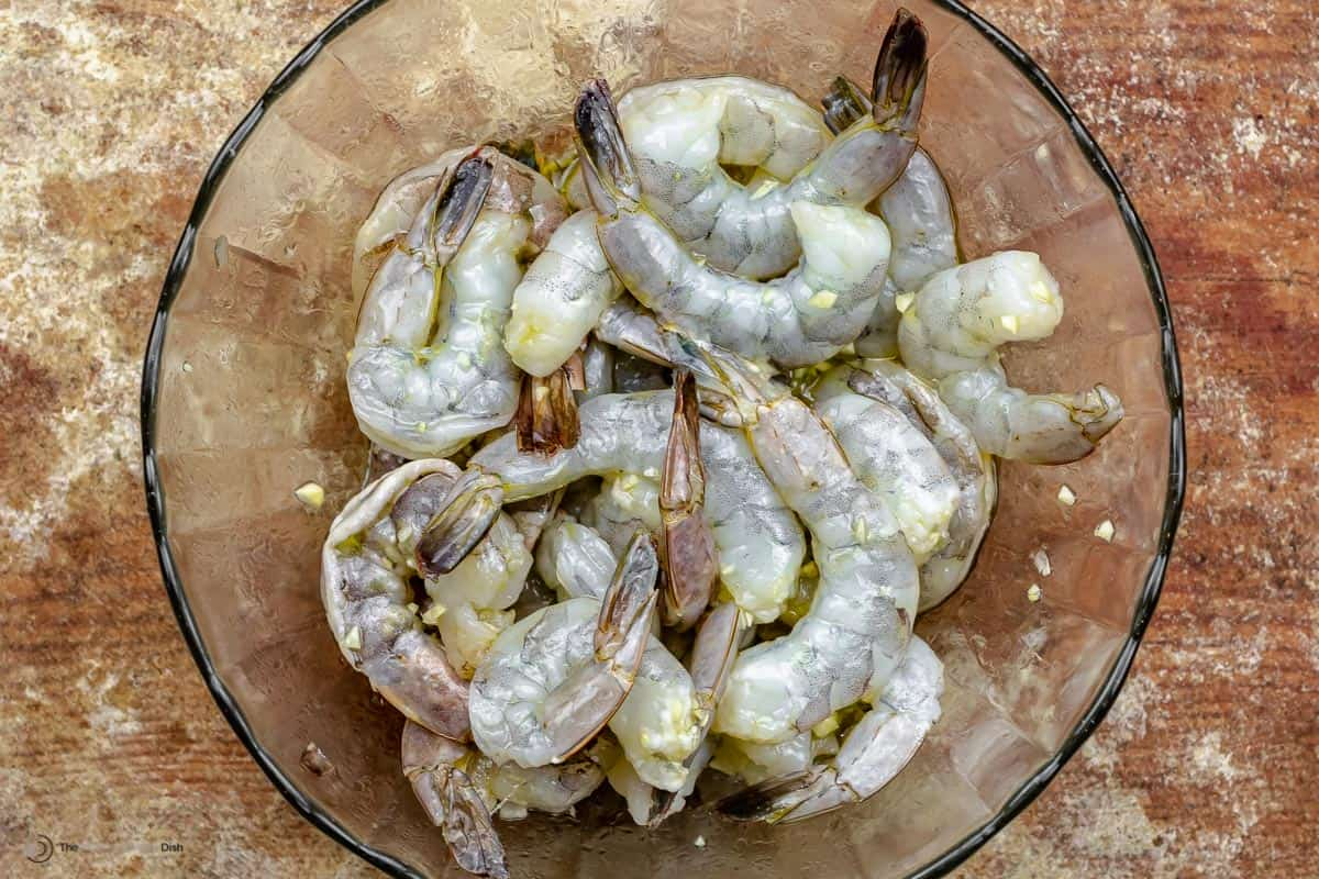 Raw shrimp marinating in olive oil and garlic