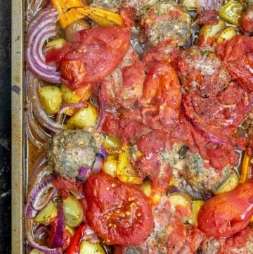 Close-up of baked meatballs with tomatoes and other vegetables in a sheet pan