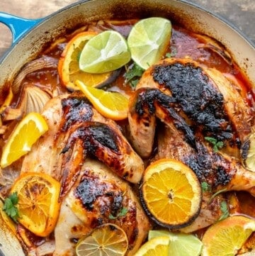 Roasted chicken with rosemary and citrus slices of orange and lime in a braising pan
