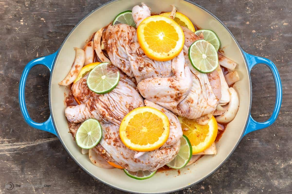 Marinated chicken with orange and lemon slices in the pan ready to bake