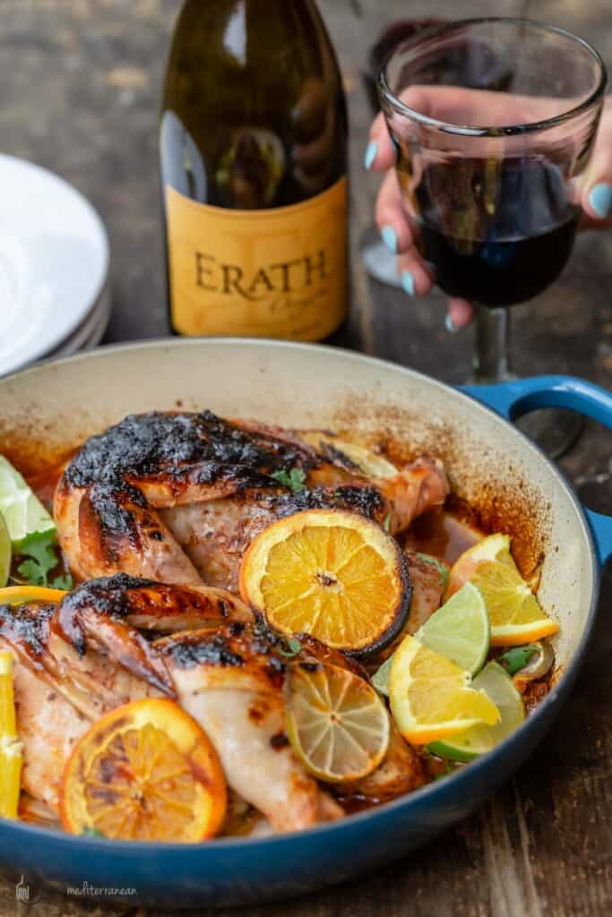 Roasted chicken with rosemary and citrus in a braising pan with a bottle of wine and a glass of wine held by a hand next to it
