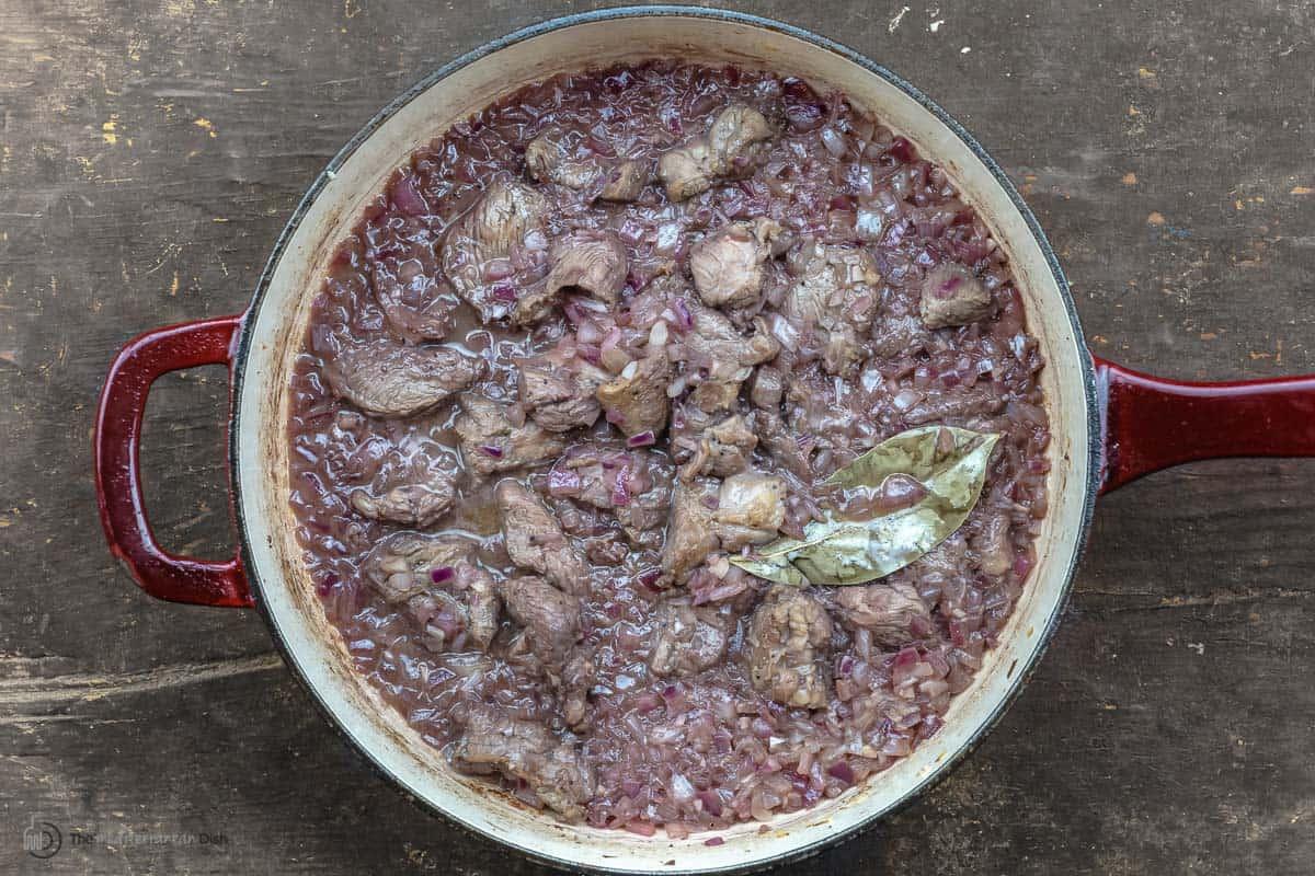 Greek lamb stew ingredients simmering in a skillet