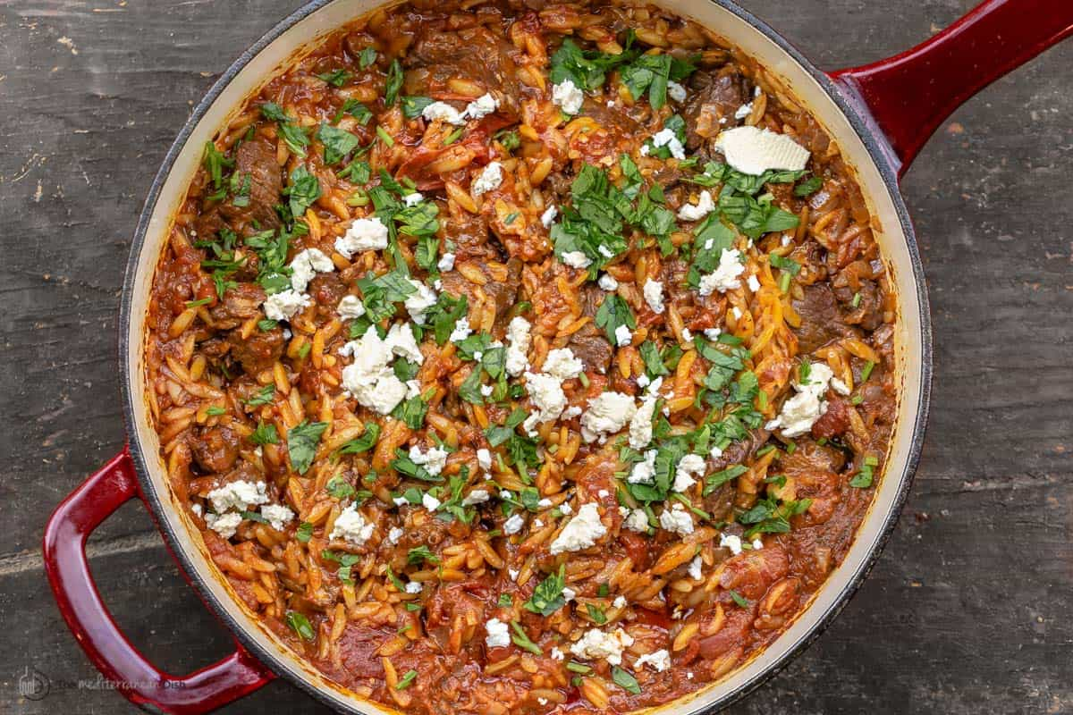 Overhead view of youvetsi garnished with feta and parsley