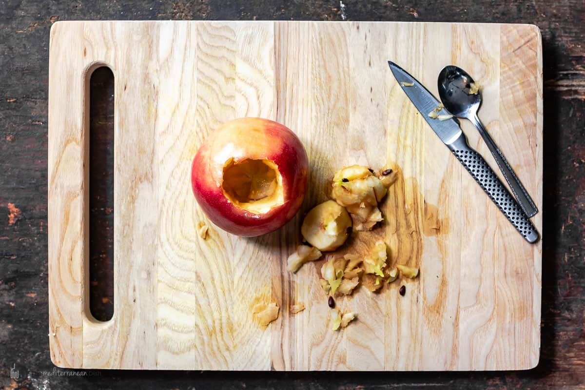 One apple cored on a cutting board