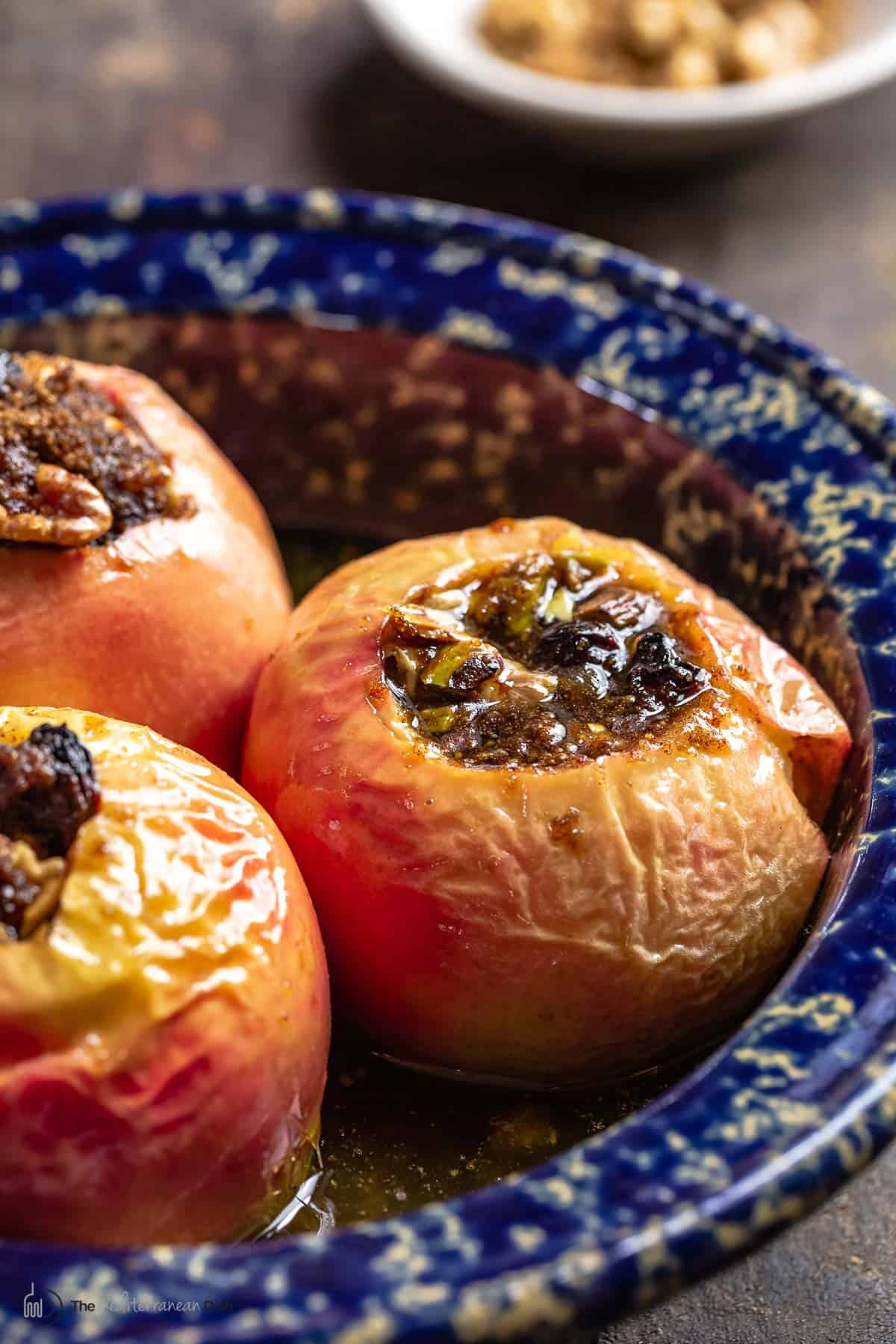 Baked apples in their blue baking dish with another small dish of extra nuts to the side