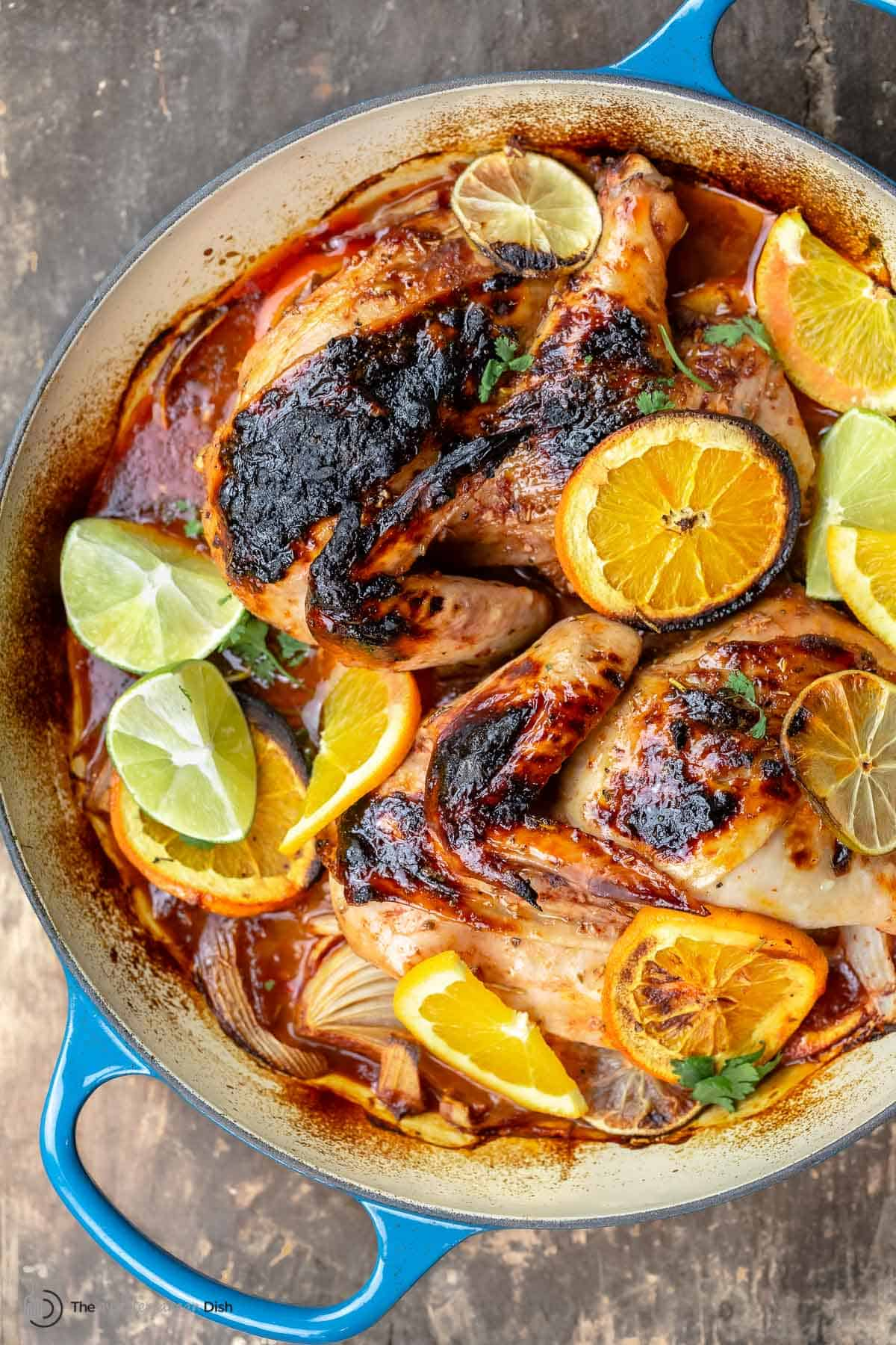 Roasted chicken with rosemary and citrus slices in a braiser