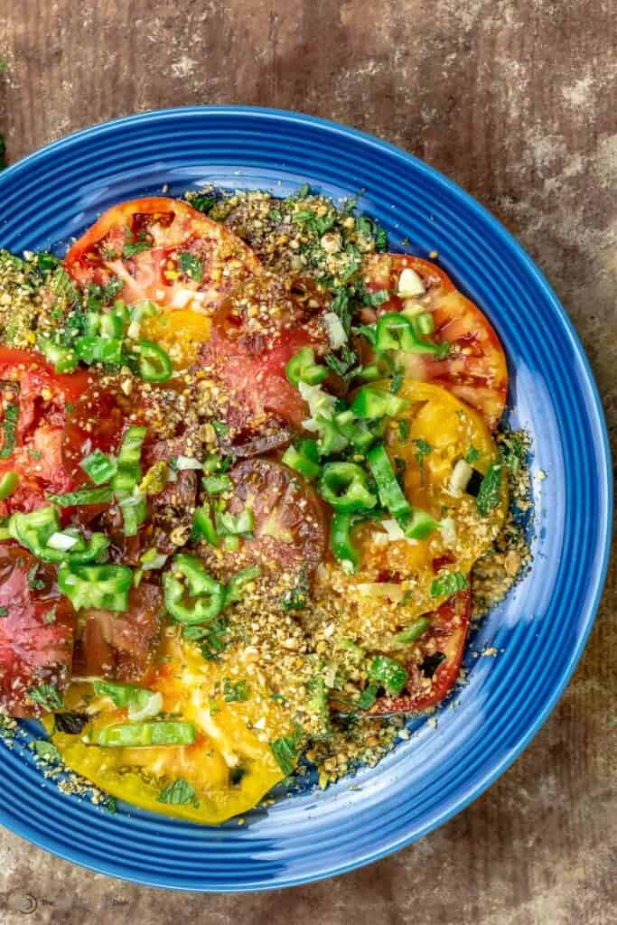 Heirloom tomato salad on a blue plate, topped with dukkah and jalapeno peppers