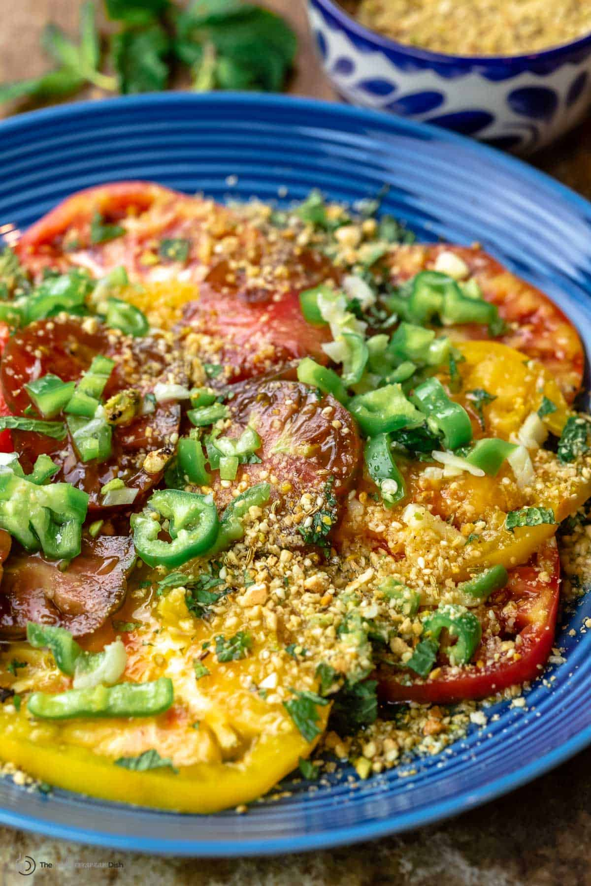 fresh tomato salad with a side of dukkah in a bowl