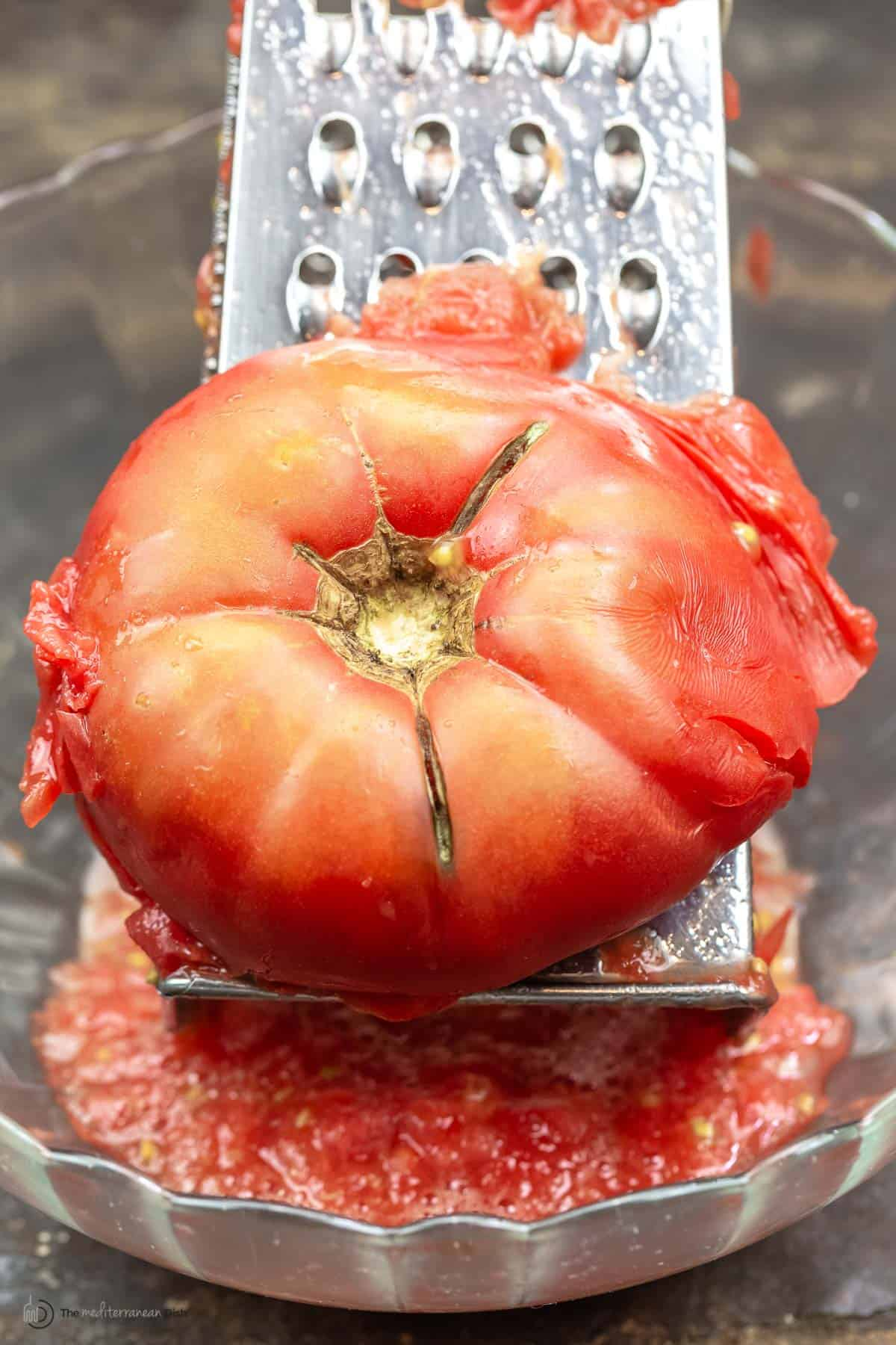 Close up of a tomato over a hand grater
