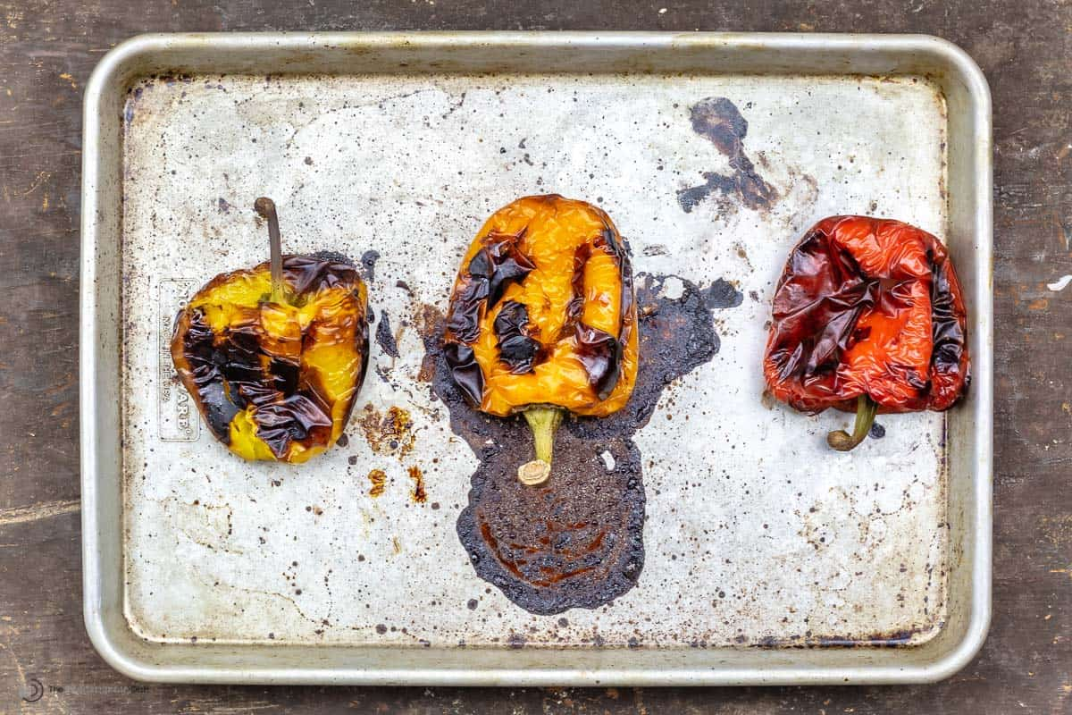 Three roasted red peppers on a sheet pan